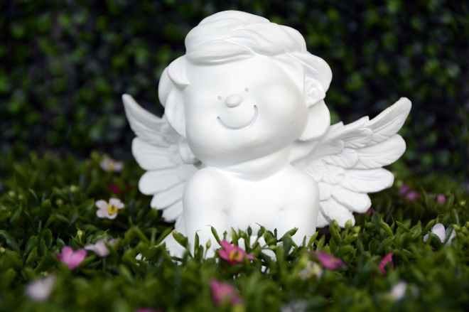 white angel ceramic figurine on green grass with white and purple flower