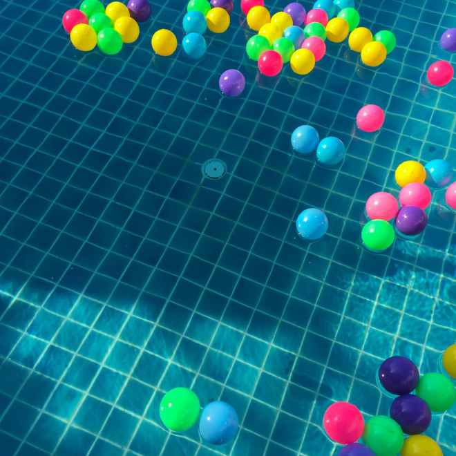 assorted color balls floating on water