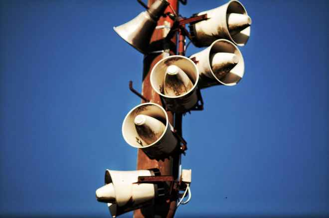 megaphone speakers on wooden post